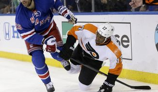 New York Rangers' Dominic Moore, left, and Philadelphia Flyers' Wayne Simmonds try to disentangle themselves during the third period of Game 5 of an NHL hockey first-round playoff series on Sunday, April 27, 2014, in New York. The Rangers defeated the Flyers 4-2. (AP Photo/Seth Wenig)