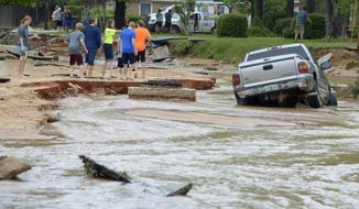 Residents walk near a truck stuck in deep water and mud on Piedmont Street after flood-water damage caused by torrential rains in Pensacola, Fla., Wednesday, April 30, 2014. (AP Photo/G.M. Andrews)
