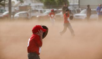 Austin Vanley, 5, covers his face from the flying sand while playing baseball in League 42's inaugural game Monday, April 28, 2014, in Wichita, Kan. National Weather Service in Wichita says the wind in Wichita got up to 52 mph. (AP Photo/The Wichita Eagle, Jaime Green) LOCAL TV OUT; MAGAZINES OUT; LOCAL RADIO OUT; LOCAL INTERNET OUT