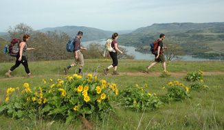 Hikers walk the trail at Coyote Wall in the Columbia River Gorge National Scenic Area on Sunday, April 20, 2014, near Bingen, Washington. (AP Photo/ The Columbian, Allen Thomas)