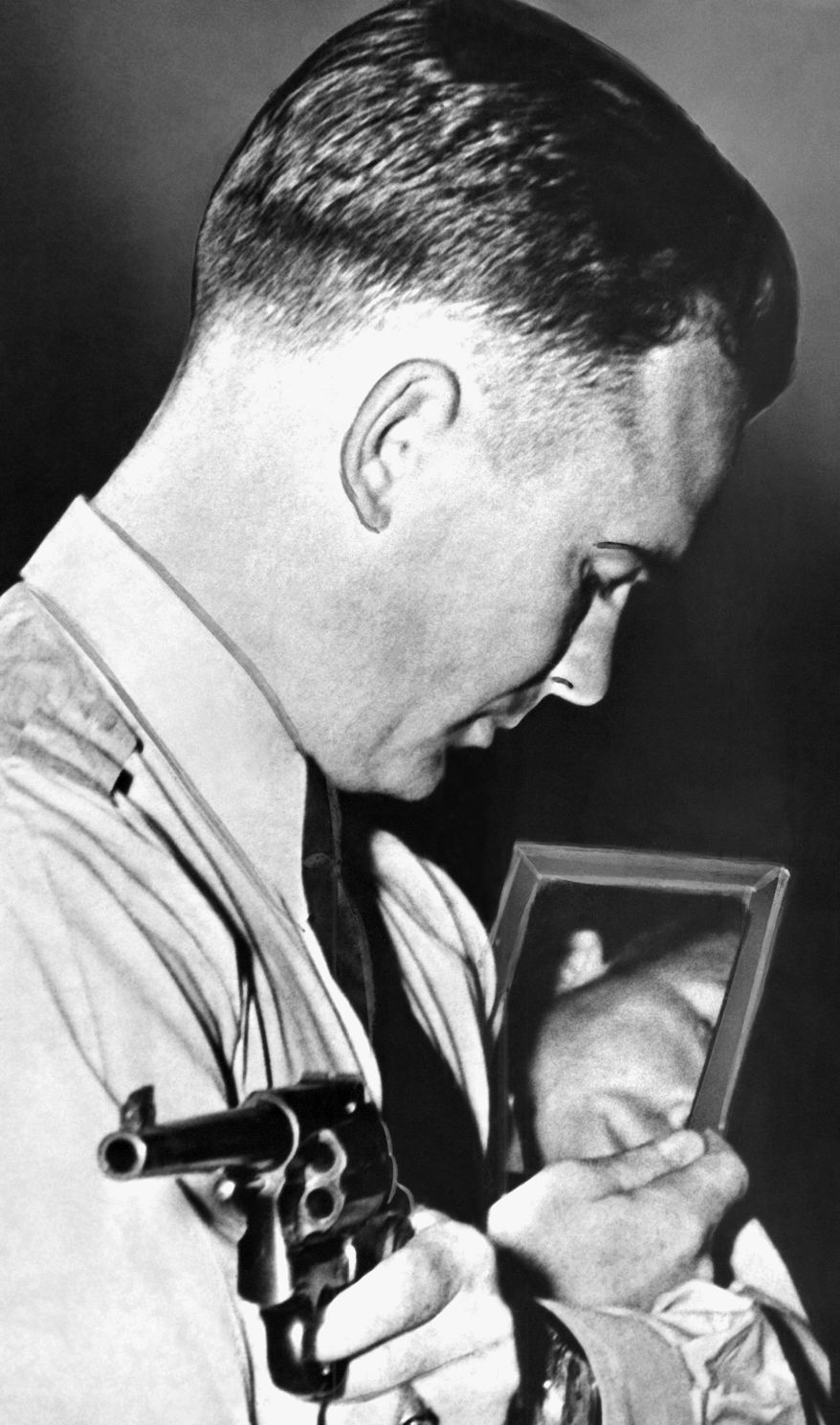 Federal Agent Walter Walsh during a demonstration at Quantico, Va., in October 1937 and shows him as he takes aim in a mirror. Walsh was shot in the shoulder at Bangor, Maine on Oct. 12, 1937, in a gun battle during which Al Brady, leader of a band of Midwest outlaws, and a henchman were shot to death, and a third gunman apprehended. (AP Photo)