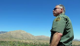 U.S. Border Patrol Tucson Sector Chief Manuel Padilla looks out over the desert terrain in the Buenos Aires National Wildlife Refuge, Wednesday, April 30, 2014, near Sasabe, Ariz. Padilla and other Border Patrol officials spent the day discussing the dangers for people trying to cross the border illegally from Mexico into the U.S., after they enter the remote desert terrain. (AP photo/Brian Skoloff)