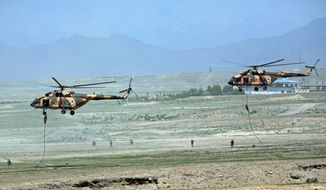 Afghan National Army (ANA) helicopters deploy soldiers during a military exercise on the outskirts of Kabul, Afghanistan, Wednesday, April 30, 2014. The Afghan National Security Forces depend exclusively on billions of dollars in funding from the United States and its allies, money that is now at risk after President Hamid Karzai's refusal to sign a security agreement to keep a small U.S. force of trainers in the country after the NATO-led coalition ends its mission and withdraws at the end of the year. (AP Photo/Massoud Hossaini)