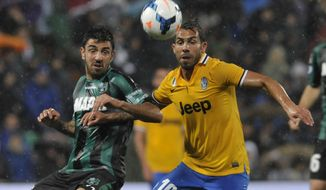 Sassuolo's Francesco Magnanelli, left, vies for the ball with Juventus's Carlos Tevez of Argentina, during their Serie A soccer match at Reggio Emilia's Mapei stadium, Italy, Monday, April 28, 2014. (AP Photo/Marco Vasini)