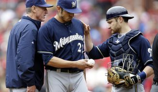 Milwaukee Brewers starting pitcher Matt Garza, center, gets a pat on the back from catcher Jonathan Lucroy while leaving a baseball game due to an injury as manager Ron Roenicke, left, stands by during the fourth inning of a baseball game against the St. Louis Cardinals Wednesday, April 30, 2014, in St. Louis. (AP Photo/Jeff Roberson)