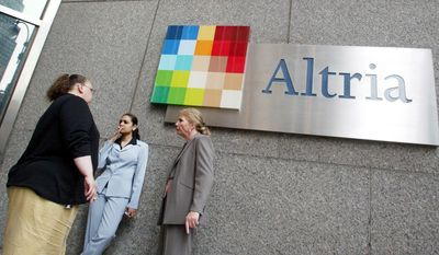 """CORRECTS DATE OF REINSTATEMENT TO APRIL 29 INSTEAD OF APRIL 2  - FILE - In this May 12, 2004 file photo people smoke near the logo for Altria Group Inc., the parent of tobacco company Phillip Morris, at the companies offices in New York.  An Illinois appellate court on Tuesday, April 29, 2014 reinstated a decade-old $10.1 billion verdict in a class-action lawsuit against Phillip Morris USA that found the nation's biggest cigarette maker misled customers about """"light"""" and """"low tar"""" designations. Philip Morris swiftly decried Tuesday's ruling by a three-judge panel of the Mount Vernon-based 5th District Appellate Court, saying it would ask the Illinois Supreme Court to review the matter. (AP Photo/Diane Bondareff, File)"""
