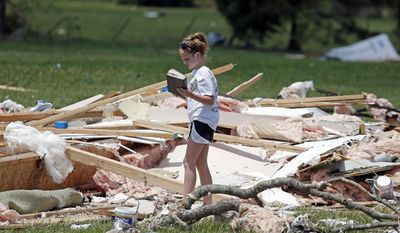 Anna Beth O'Neal, 11, salvages a Bible from the remains of Grace Falls Church on Tuesday, April 29, 2014, after it was destroyed by storms Monday in Fayetteville, Tenn.  On Sunday evening, roughly 15 tornadoes carved a path of destruction in the South and the country's midsection, according to estimates from the National Oceanic and Atmospheric Administration's Storm Prediction Center. On Monday, around 50 tornadoes ravaged the South, the agency said.  (AP Photo/Mark Humphrey)