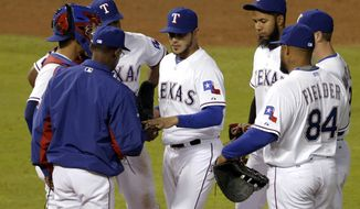 Texas Rangers manager Ron Washington, left, takes the ball from starting pitcher Martin Perez in the fifth inning of a baseball game against the Oakland Athletics as Robinson Chirinos, from left, Adrian Beltre, Elvis Andrus, Josh Wilson and Prince Fielder (84) stand near, Tuesday, April 29, 2014, in Arlington, Texas. (AP Photo/Tony Gutierrez)