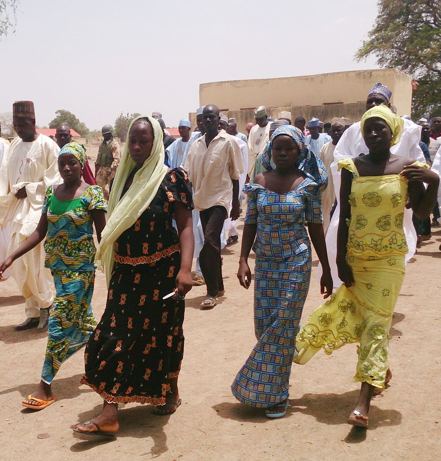 ** FILE ** In this Monday April 21, 2014, file photo, four female students of the government secondary school Chibok, who were abducted by gunmen and reunited with their families, walk in Chibok, Nigeria. (AP Photo/ Haruna Umar, File)