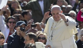 Pope Francis salutes the faithful as he arrives for his weekly general audience,  in St. Peter's square at the Vatican,  Wednesday, April 30, 2014. (AP Photo/Andrew Medichini)