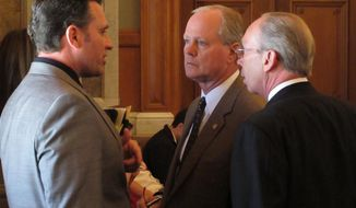 Kansas state Sen. Ty Masterson, left, an Andover Republican, confers with state Reps. Gene Suellentrop, center, a Wichita Republican, and Marvin Kleeb, right, an Overland Park Republican, during the House's session, Thursday, May 1, 2014, at the Statehouse in Topeka, Kan. Masterson is the Senate's lead negotiator on budget issues, and Suellentrop and Kleeb represent House Republicans in the talks. (AP Photo/John Hanna)