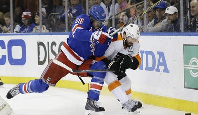 New York Rangers' Brad Richards (19) and Philadelphia Flyers' Adam Hall (18) fight for control of the puck during the first period in Game 7 of an NHL hockey first-round playoff series on Wednesday, April 30, 2014, in New York. (AP Photo)