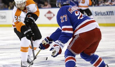 Philadelphia Flyers' Claude Giroux (28) passes through New York Rangers' Ryan McDonagh's legs during the first period in Game 5 of an NHL hockey first-round playoff series, Sunday, April 27, 2014, in New York. (AP Photo/Seth Wenig)