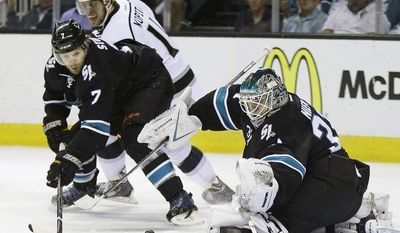 San Jose Sharks goalie Antti Niemi, right, of Finland, deflects a shot on goal next to teammate Brad Stuart (7) and Los Angeles Kings' Anze Kopitar, during the second period in Game 7 of an NHL hockey first-round playoff series on Wednesday, April 30, 2014, in San Jose, Calif. (AP Photo/Marcio Jose Sanchez)