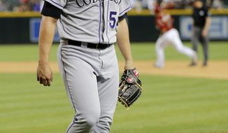 Colorado Rockies pitcher Tommy Kahnle walks off the field as Arizona Diamondbacks' Miguel Montero rounds the bases after Kahnle gave up a walk off solo home run to Montero during the 10th inning of a baseball game on Wednesday, April 30, 2014, in Phoenix. The Diamondbacks won 5-4. (AP Photo/Matt York)