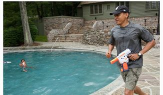 President Obama has a water gun fight with his daughter Sasha on her birthday weekend at Camp David in this June 11, 2011, file photo. (Official White House Photos by Pete Souza)