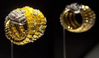 """Snake"" bracelet-watch in yellow gold and enamel, with rubies and diamonds is exhibited at the Bulgari: 130 Years of Masterpieces exhibition in the Houston Museum of Natural Science on April 29, 2014 in Houston.  Richard Burton once quipped that Elizabeth Taylor knew only one Italian word: Bulgari.  Taylor collected hundreds of fabulous jewels in her lifetime, but few as grand as the Bulgari pieces from Burton, including a platinum-and-diamond necklace centered around a 65-carat Burmese cabochon sapphire, a present for her 40th birthday.    The necklace is one of 150 one-of-a-kind creations from the Bulgari Heritage collection on display beginning Friday at the Houston Museum of Natural Science in ""Bulgari: 130 Years of Masterpieces."" A section of the exhibit is devoted to Taylor's famous pieces from the Italian jeweler.  (AP Photo/Houston Chronicle, Marie D. De Jesus) MANDATORY CREDIT"