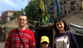 Andriy Poklonov, 35, his daughter Sofia, 8, and wife Evhenia, 35, pose for a photo in Kiev, Ukraine, Thursday, May 1, 2011. Despite the danger of war with Russia, the fear of losing more of their territory and tough economic times ahead, many Ukrainians in the center and west of the country are convinced that their country is moving in the right direction toward becoming a law-abiding European nation. (AP Photo/Maria Danilova)