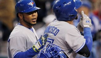 Toronto Blue Jays' Edwin Encarnacion, left, congratulates designated hitter Juan Francisco after his two-run home run off Kansas City Royals starting pitcher Jeremy Guthrie during the fourth inning of a baseball game in Kansas City, Mo., Thursday, May 1, 2014. (AP Photo/Orlin Wagner)