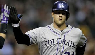 Colorado Rockies pitcher Jordan Lyles crosses home plate after hitting a home run against the Arizona Diamondbacks during the third inning of a baseball game on Wednesday, April 30, 2014, in Phoenix. (AP Photo/Matt York)