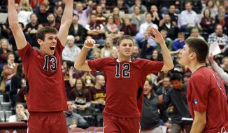 Stanford's Eric Mochalski (13) and Steven Irvin (12) celebrate after Conrad Kaminski scored against BYU during the fourth set of an NCAA men's college volleyball tournament semifinals in Chicago on Thursday, May 1, 2014. (AP Photo/Nam Y. Huh)