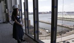 Whitney Museum curatorial assistant Christie Mitchell looks out on the Hudson River from the future board room during a tour of the future site for the Whitney Museum, Thursday, May 1, 2014, in New York. The museum will open in its new location in lower Manhattan in the spring of 2015.(AP Photo/Julie Jacobson)