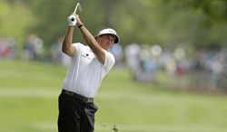Phil Mickelson watches his approach shot on the fourth hole during the first round of the Wells Fargo Championship golf tournament in Charlotte, N.C., Thursday, May 1, 2014. (AP Photo/Chuck Burton)