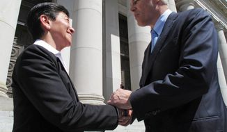 King County Superior Court Judge Mary Yu, left, and Gov. Jay Inslee grasp hands on the steps of the Washington state Supreme Court after the announcement of Yu's  appointment to the high court, on Thursday, May 1, 2014, in Olympia, Wash. Yu, who will be sworn in later this month, will be the first gay justice, and the first Asian American, to serve on the court. (AP Photo/Rachel La Corte)