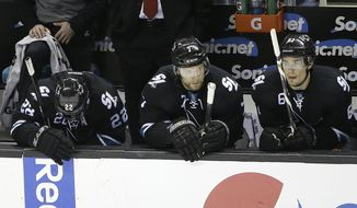 San Jose Sharks defenseman Dan Boyle, from left, defenseman Brad Stuart, and defenseman Justin Braun sit on the bench during the third period of Game 7 of an NHL hockey first-round playoff series in San Jose, Calif., Wednesday, April 30, 2014. The Kings won 5-1. (AP Photo)