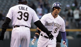 Colorado Rockies third base coach Stu Cole (39) congratulates Rockies' Carlos Gonzalez (5) after Gonzalez's home run in the first inning of a baseball game against the New York Mets in Denver, Thursday, May 1, 2014.(AP Photo/Joe Mahoney)