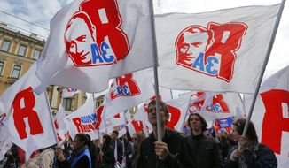 Members of pro-Kremlin movement Young Guard carry flags depicting Russian President Vladimir Putin during a May Day rally in St. Petersburg, Russia, Thursday May 1, 2014. The flag reads: 'I Support!'. (AP Photo/Dmitry Lovetsky)