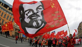 Communists carry a flag depicting Vladimir Lenin, the Soviet Union founder, during a tradition May Day march in St.Petersburg, Russia, Thursday, May 1, 2014. (AP Photo/Dmitry Lovetsky)