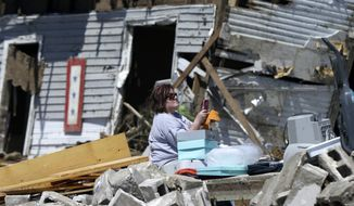 """Sandra Hedrick looks at her mobile telephone as she sits in storm debris in Vilonia, Ark., Thursday, May 1, 2014. Forecasters say a tornado that hit Little Rock's suburbs and killed 15 people had winds approaching 200 mph. Sunday's storm was rated as a """"high-end"""" EF4 on a scale of tornado strength. (AP Photo/Danny Johnston)"""