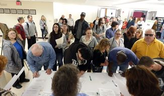 In this April 22, 2014, photo, job seekers line up for a job fair at Columbia-Greene Community College in Hudson, N.Y. (AP Photo/Mike Groll)