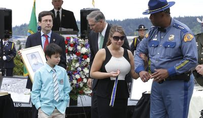 Washington State Patrol Chief John Batiste, right, escorts Alissa O'Connell, second from right, and her son Kian, 8, lower left, after O'Connell was given a state law enforcement medal of honor by Gov. Jay Inslee, third from right, and Attorney General Bob Ferguson, upper left, on behalf of her husband, Trooper Sean O'Connell Jr., lower right, who was killed May 31, 2013, in a motorcycle accident while he was helping with a traffic detour around the collapsed Skagit River Bridge, during the annual law enforcement medal of honor ceremony, Friday, May 2, 2014 at the Capitol in Olympia, Wash.  (AP Photo/Ted S. Warren)