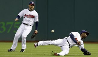 Cleveland Indians' Michael Bourn, right, dives for but cannot catch a single hit by Chicago White Sox's Alexei Ramirez in the fourth inning of a baseball game on Friday, May 2, 2014, in Cleveland. Indians' Ryan Raburn, left, watches. (AP Photo/Tony Dejak)