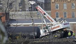 Workers remove damaged tanker cars along the tracks where several CSX tanker cars carrying crude oil derailed and caught fire along the James River near downtown Lynchburg, Va., Thursday, May 1, 2014.  Virginia state officials were still trying Thursday to determine the environmental impact of the train derailment.  (AP Photo/Steve Helber)
