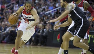 This photo taken March 15, 2014 shows Washington Wizards guard Andre Miller (24) driving to the basket against Brooklyn Nets guard Deron Williams (8) during the second half of an NBA basketball game in Washington. When the Washington Wizards split up by position for meetings before Game 1 against first-round playoff opponent Chicago, starting guards John Wall and Bradley Beal listened while veteran Miller spoke. After all, twentysomethings Wall and Beal were about to be in the NBA postseason for the first time; the 38-year-old Miller was getting set for his 10th playoff series. All three, though, had something in common. (AP Photo/ Evan Vucci)