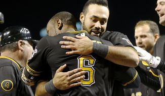 Pittsburgh Pirates' Starling Marte (6) gets a hug from Pedro Alvarez, right, after Marte hit the game-winning home run in the bottom of the ninth inning of the baseball game against the Toronto Blue Jays on Friday, May 2, 2014, in Pittsburgh. Alvarez had hit a two-run homer earlier in the inning to tie the game. The Pirates won 6-5. (AP Photo/Keith Srakocic)