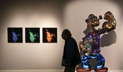 A prospective buyer browses gallery space featuring Andy Warhol's Six Self Portraits and Jeff Koons' Popeye during a preview exhibition for Sotheby's Spring Evening Sale of impressionistic and modern art, Friday, May 2, 2014, in New York. The sale will begin on May 7. (AP Photo/Julie Jacobson)