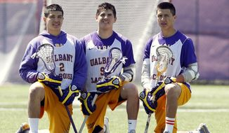 In this photo taken on Monday, April 28, 2014, University at Albany lacrosse players Miles Thompson (2), Ty Thompson (91) and Lyle Thompson (4) pose after practice in Albany, N.Y.  The trio of Native American players, Miles, younger brother Lyle, and cousin Ty, have transformed Albany into an offensive juggernaut in Division I men's lacrosse. (AP Photo/Mike Groll)