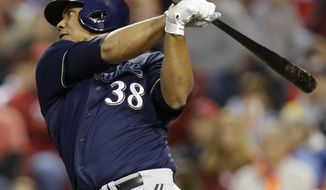 Milwaukee Brewers' Wily Peralta hits a double off Cincinnati Reds starting pitcher Mike Leake to drive in two runs in the fifth inning of a baseball game on Friday, May 2, 2014, in Cincinnati. (AP Photo/Al Behrman)