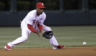 Philadelphia Phillies' Jimmy Rollins fields a ground ball hit by Washington Nationals' Danny Espinosa and throws to second to get out Nationals' Jayson Werth in the fourth inning of a baseball game on Friday, May 2, 2014, in Philadelphia. (AP Photo/Laurence Kesterson)