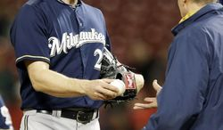Milwaukee Brewers relief pitcher Jim Henderson, left, is taken out by manager Ron Roenicke in the eighth inning of a baseball game against the Cincinnati Reds, Thursday, May 1, 2014, in Cincinnati. Henderson was the losing pitcher in the game won by Cincinnati 8-3. (AP Photo/Al Behrman)
