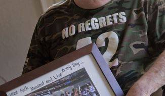 ADVANCE FOR WEEKEND EDITIONS, MAY 3-4 - FILE - In this Aug 15, 2011, file photo, Sheldon Davidson holds a photograph of his first Pat's Run marathon in 2009 at his home in Mesa, Ariz. Pat's Run is filled with inspirational stories all wanting to honor the memory of NFL star-turned-soldier Pat Tillman. For seven years, Davidson had become the annual exclamation point to the run, climbing out of his wheelchair and dragging the paralyzed left side of his body across the final 42 yards. He died 42 days before this year's run, so his wife and daughter made the journey without him, honoring two heroes with every step. (AP Photo/Matt York)
