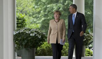 President Barack Obama and German Chancellor Angela Merkel walk from the Oval Office of the White House in Washington, Friday, May 2, 2014, to their joint news conference in the Rose Garden. Obama and Merkel are putting on a display of trans-Atlantic unity against an assertive Russia, even as sanctions imposed by Western allies seem to be doing little to change Russian President Vladimir Putin's reasoning on Ukraine. (AP Photo/Carolyn Kaster)