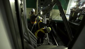 South Korea's subway workers try to repair a train after its collision at Sangwangshipri station in Seoul, South Korea, Friday, May 2, 2014. A subway train plowed into another train stopped at the station Friday, causing minor injuries for scores of people, a city official said. (AP Photo/Lee Jin-man)