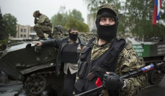 Pro-Russian gunmen guard the central square of Slovyansk, eastern Ukraine, Friday, May 2, 2014. Fighting broke out around dawn near Slovyansk, a city 160 kilometers (100 miles) from the Russian border that has become the focus of the armed insurgency. Two helicopter crew members were killed in the crashes, both sides said, and the insurgents reported one member killed. (AP Photo/Alexander Zemlianichenko)