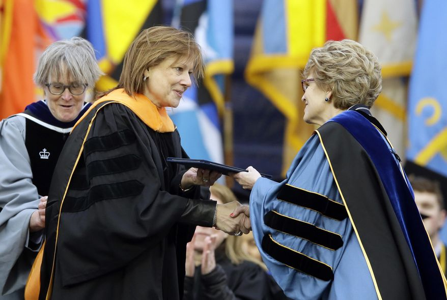 General Motors CEO Mary Barra, left, is conferred an honorary Doctor of Engineering degree by Michigan President Mary Sue Coleman, before addressing the University of Michigan graduates at a commencement ceremony Saturday, May 3, 2014 in Ann Arbor, Mich. Barra, the first woman to lead a major automaker, took the top spot at GM in January, just as a deadly ignition switch problem was starting to surface. Barra urged the students to be honest in every aspect of their lives, and to use their optimism and propensity for inclusion to rethink outdated assumptions and expose and correct injustice. (AP Photo/Carlos Osorio)