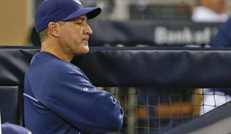 San Diego Padres hitting coach Phil Plantier is solemn in the dugout during the ninth inning of a baseball game in which the Padres were shutout 2-0 by the Arizona Diamondbacks Friday, May 2, 2014, in San Diego. The Padres are the lowest scoring team in Major League Baseball.  (AP Photo/Lenny Ignelzi)